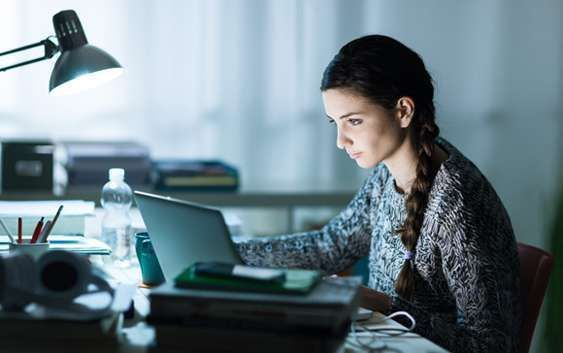 Mulher em casa mexendo no computador